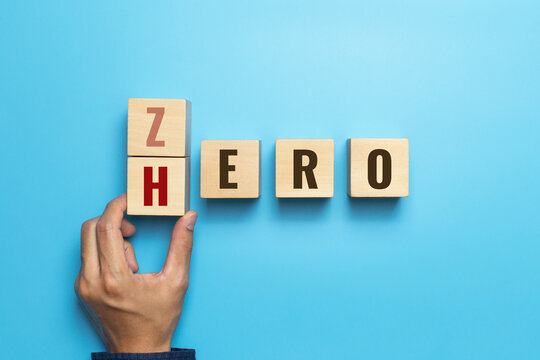 Hand slid wooden cube with the word ZERO to HERO on blue background. Change for the better. Concept of personal development