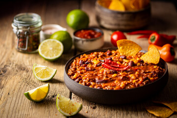 Mexican hot chili con carne in a bowl with tortilla chips on wooden background