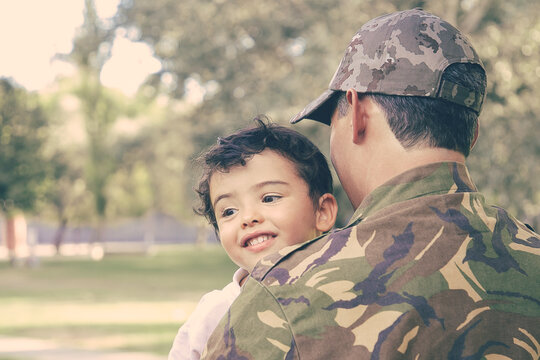 Back view of Caucasian man holding kid and wearing army uniform. Cheerful little boy sitting on father hands, hugging dad and smiling happily. Family reunion, fatherhood and returning home concept