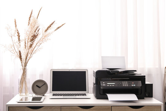 Modern printer, laptop and office supplies on white table indoors