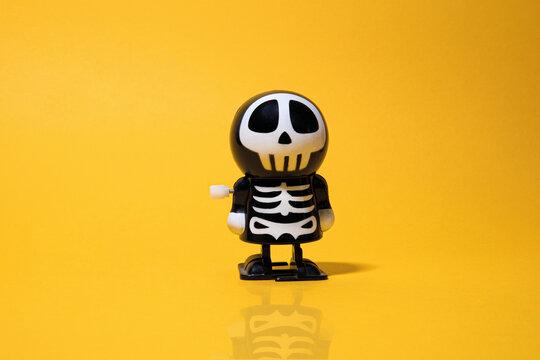 Halloween, plastic toy for children. Skeleton and skull, yellow background