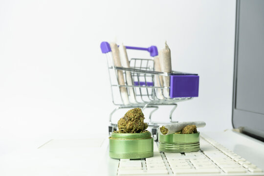 Grinder with marijuana buds and joints in shopping cart on laptop keyboard.Medical cannabis marijuana alternative medicine.Shopping online , weed store concept on white background.