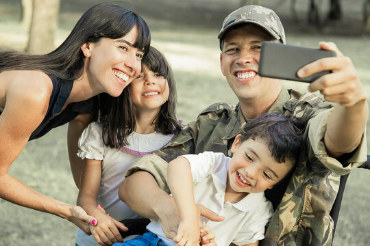 Joyful happy disabled military man taking selfie with his wife and two kids in park. Family togetherness and support concept