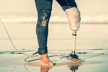 Cropped male surfer standing with surfboard on sea beach. Unrecognizable amputee with artificial leg walking along coastline with board. Physical disability, lifestyle and extreme sport concept Fotobehang