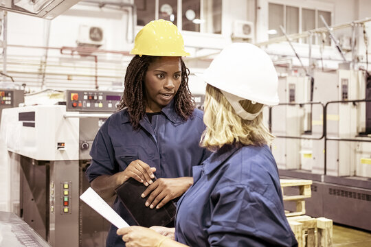 Diverse female factory employees in hardhats and overalls standing on plant floor and chatting. Medium shot. Industrial occupation concept