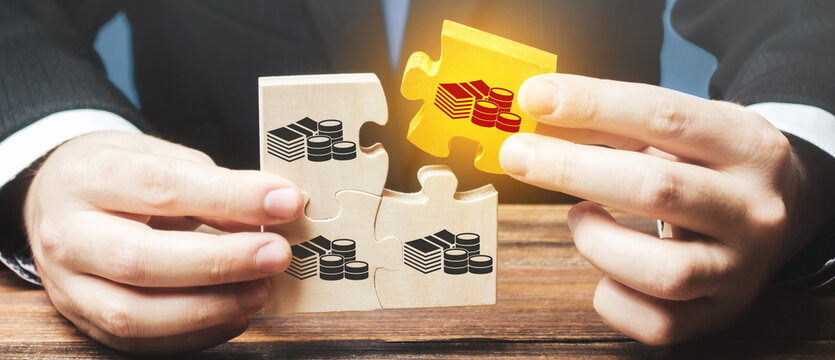 Businessman holds the wooden puzzle with a picture of money. The concept of financial management and distribution of funds. Saving and investing. Property division. Divorce and legal services