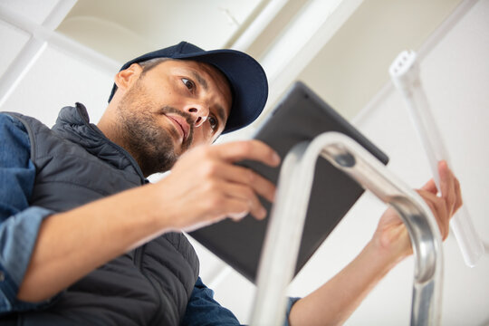 male electrician holding tablet and fluorescent bulb