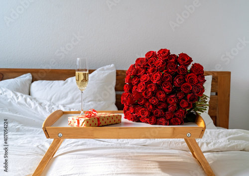 Romantic surprise on Valentine Day. Wrapped gift, bouquet of red roses and glass of champagne on tray on bed. Celebrating Mother's day or International women day