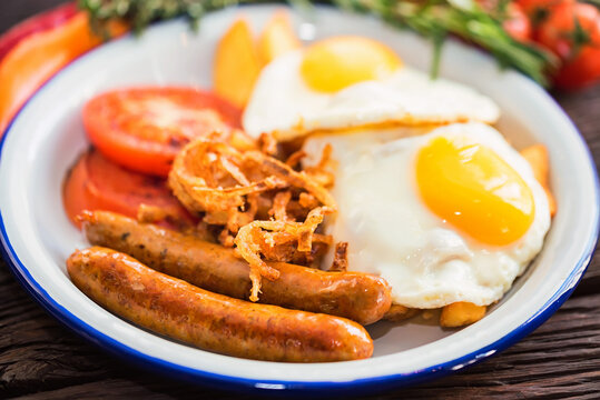Typial breakfast with eggs, tomato, onion rings and sausage on plate