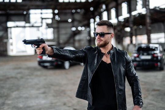 Brutal male points a gun on a point. Man dressed in leather black jacket and fashion glasses. Broken building with no windows on a background.