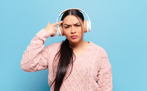 hispanic woman feeling confused and puzzled, showing you are insane, crazy or out of your mind