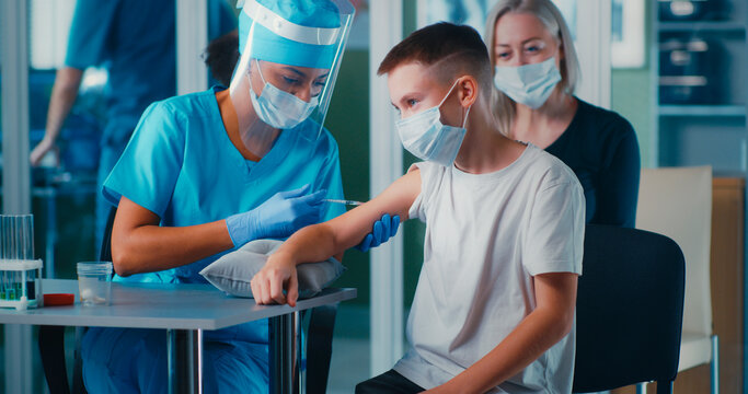 Black doctor vaccinating boy near mother