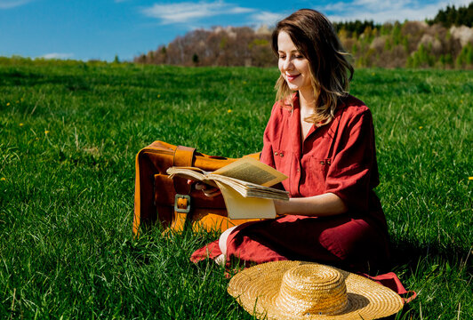Beautiful girl in red dress and hat with suitcase and book sitting on meadow