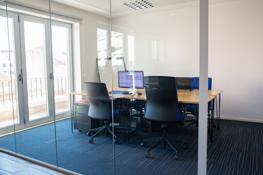 Empty boardroom behind glass wall. Meeting room with conference table, shared desk for team and workplaces. Trading graphs on monitor. Office interior or commercial real estate concept