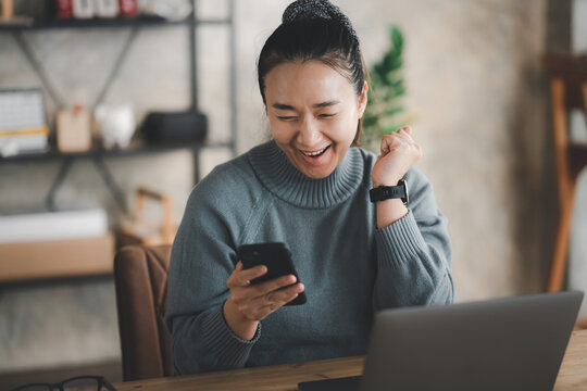 Excited happy Asian woman looking at phone screen, celebrating online win, overjoyed young female screaming with joy, holding smartphone, reading good news in unexpected message or email