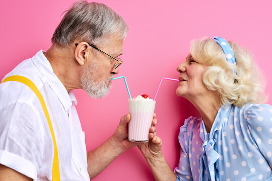 couple enjoying milk cocktail drinking from one glass with two straws, elderly man and woman on date. 14 february, st valentines day concept, love. isolated on pink background