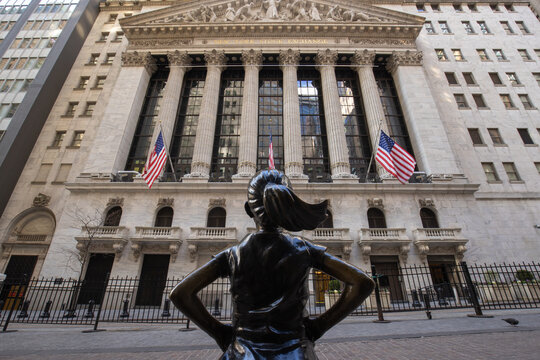 Fearless Girl sculpture in front of New York Stock Exchange building in Wall Street area