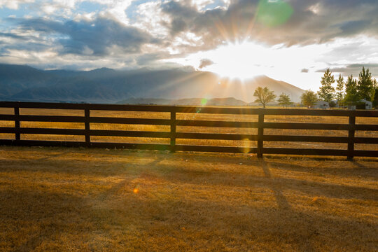 Post and rail fence across farm backlit by setting sun