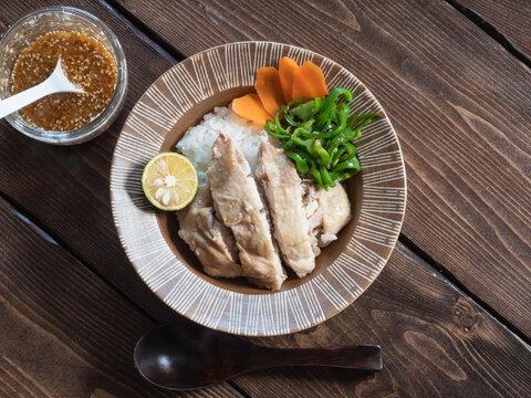 ご飯の上に乗せた鶏肉の料理、海南鶏飯(ハイナンチキンライス)とタレ。
