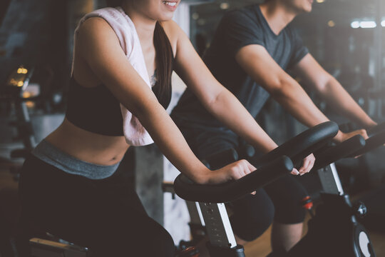 Asian man and woman they are enjoys cycling in the gym because it keeps his legs strong and healthy.
