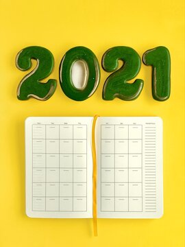 Month calendar in planner, green with golden gingerbread in a shape of numbers 2021, yellow background