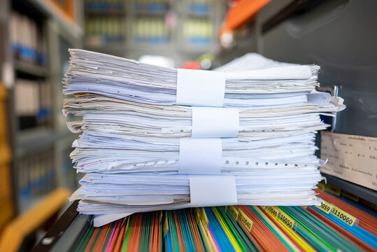 Many documents are stacked in the office.