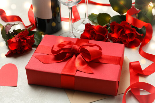 Concept of Valentine's day with roses, wine and gift box on white textured background