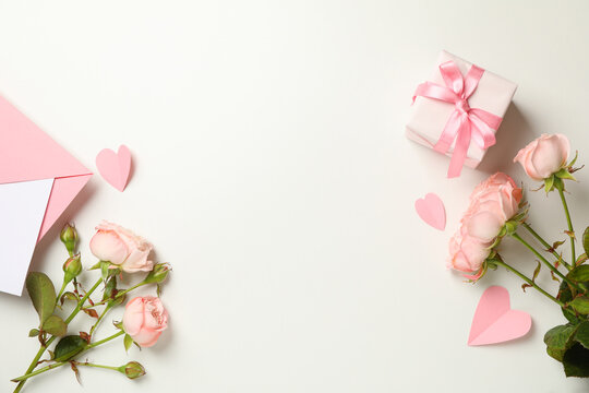 Envelope, roses, hearts and gift box on white background