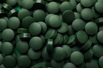 Spirulina in pills on whole background, close up