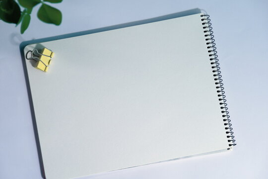 Top view of an open blank notebook, a yellow binder clip on the notebook