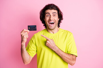 Photo of handsome brown curly haired man wear yellow t-shirt point debit card amazed isolated on pink color background Wall mural