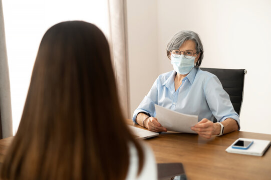 Senior female hr manager sitting at the office, wearing face mask, training young female worker intern, interviewing job seeker, checking cv, mentoring student. Social distance and safety concept