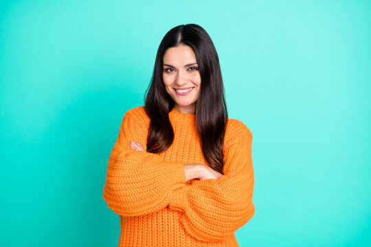 Photo of positive mature lady self-assured look camera folded arms wear orange pullover isolated teal color background