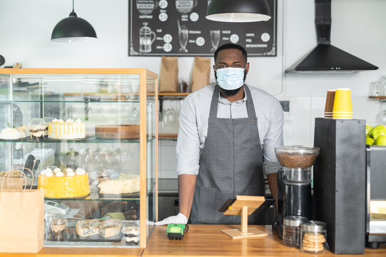 An African-American male waiter, cafe owner wearing mask and gloves stands behind the counter. A multiracial entrepreneur, bakery staff during quarantine lockdown