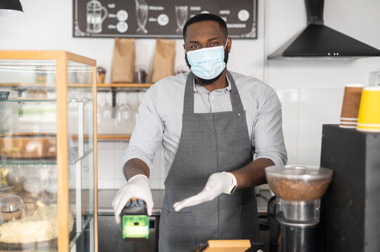 An African-American waiter wearing mask and gloves holds terminal, credit card reading bank machine offers contactless payment in pandemic. New protective rules during quarantine lockdown period