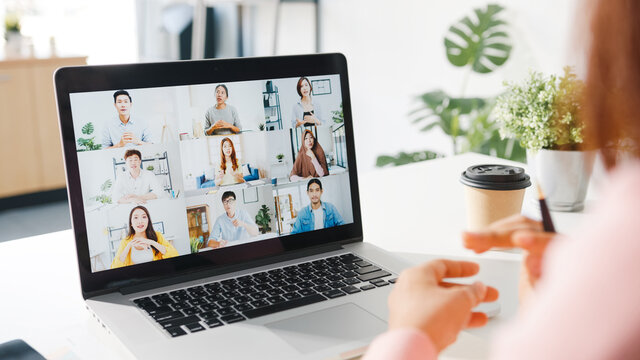 Young Asia businesswoman using laptop talk to colleague about plan in video call meeting while work from home at living room. Self-isolation, social distancing, quarantine for corona virus prevention.