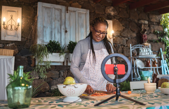 African senior woman streaming online virtual masterclass cooking lesson outdoors at home - Focus on face