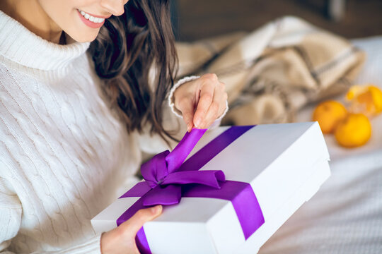 Dark-haired woman holding a gift in her hands