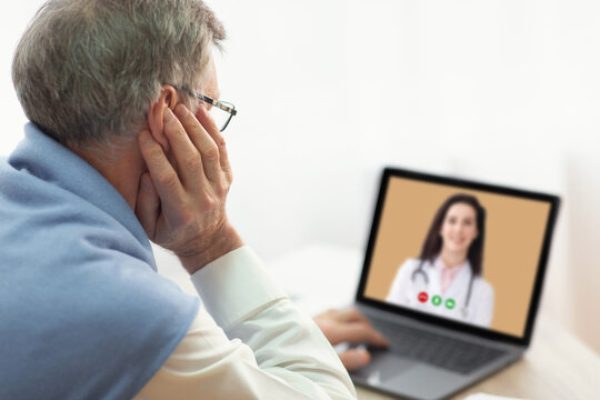 Telehealth concept. Senior man having online video call with doctor on laptop computer at home
