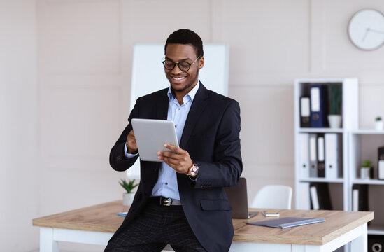 Joyful african american businessman using newest digital tablet