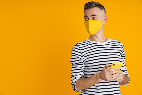 Pleased handsome man in protective mask using mobile phone