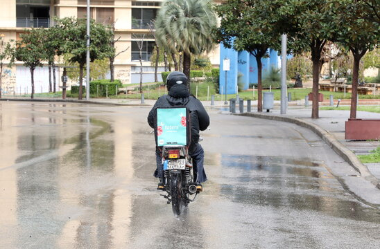 A delivery driver from the mobile app toters ride on a motorcycle, during a lockdown and a 24-hour curfew to curb the spread of the coronavirus disease (COVID-19) in Beirut