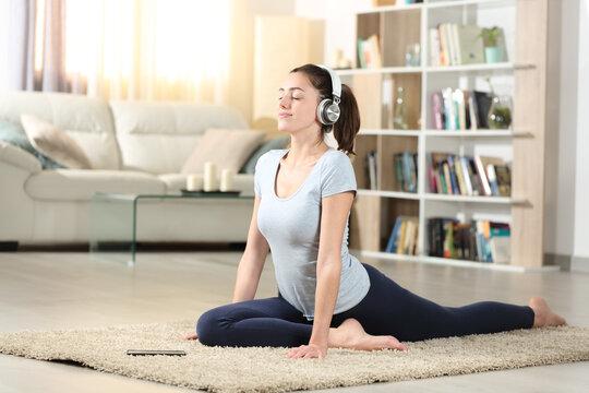 Woman doing yoga exercise listening audio tutorial