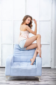 Beautiful and cute young girl on a chair in fashionable clothes with light makeup and curls