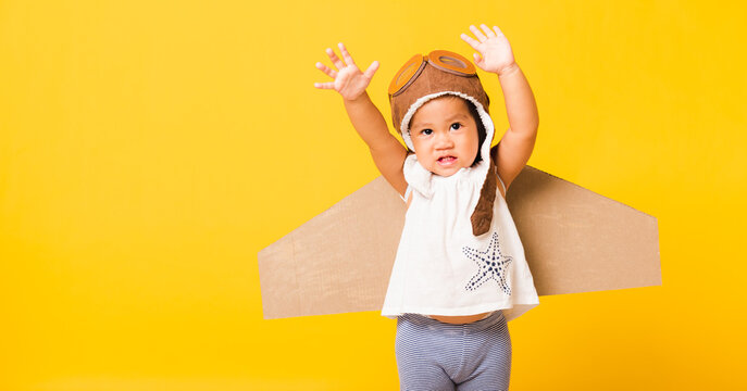 Happy Asian beautiful funny baby little girl smile wear pilot hat raise hand up play and goggles with toy cardboard airplane wings fly, studio shot isolated yellow background, Startup freedom concept