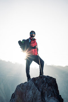 Young traveler in red snow jacket and a backpack standing on blue isolated background. Looking upwards in the sky with confidence . Confidence and success concept.