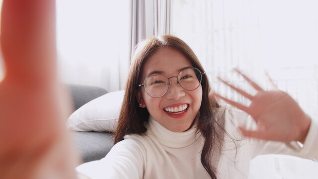Beautiful Asian woman wearing glasses is smiling and waving to the video camera for a selfie to a friend.