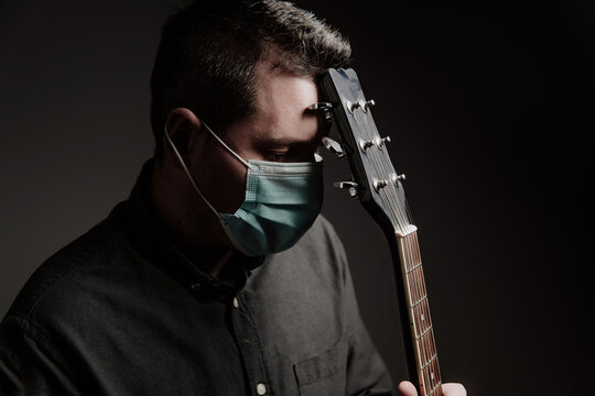 a man in a medical mask on a dark background, with an old acoustic guitar.