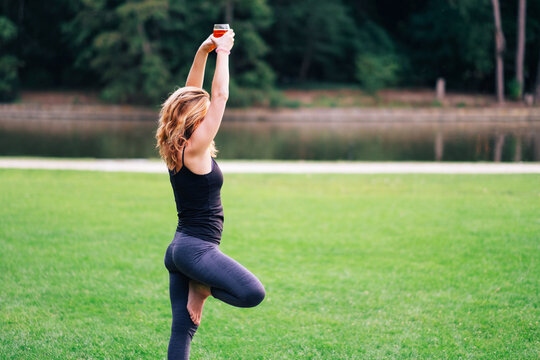 a woman practicing drunk yoga outdoor at the park. Woman holding a glass of alcohol doing pilates. New trending sports classes where people sports with wine or beer