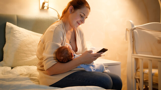 Smiling young mother feeding her newborn baby with breast milk working and browsing internet on smartphone at night in bedroom. Concept of healthy and natural baby nutrition. Health of mother and